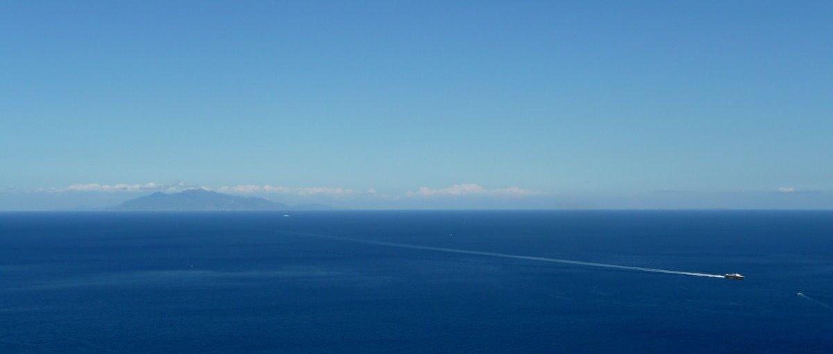 Panorama maritime vu depuis la route de la corniche à Bastia ; sur la ligne d'horizon, l'Ile d'Elbe ; à droite de l'image, le Corsica Express Seconda, bientôt rejoint par la pilotine du port